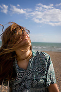 A 19 year-old girl's hair blows across her face at the beach at Brighton, England.