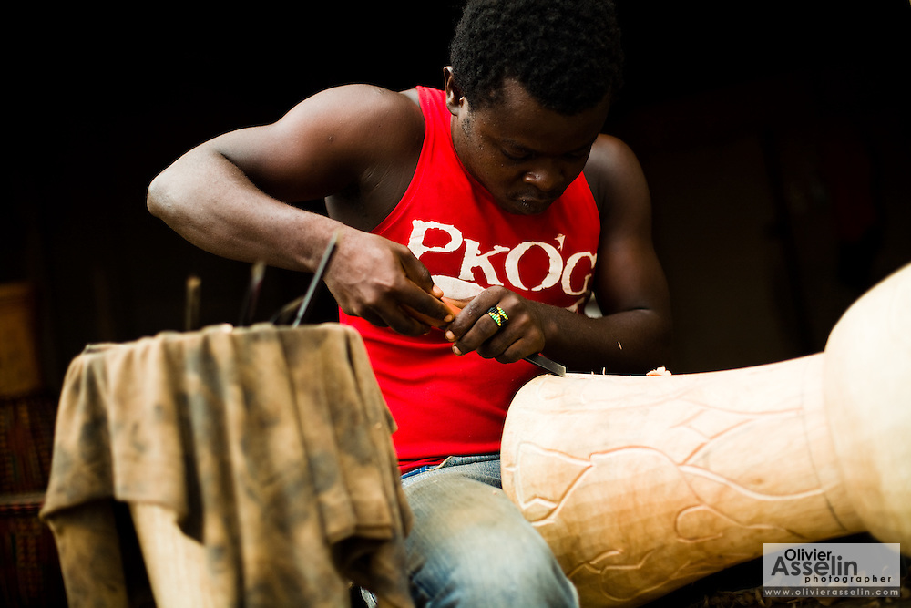 Drum-maker Michael Odametey carves a traditional drum in Accra, Ghana on Tuesday June 16, 2009.