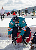 Eric Muise of the Easton Fection team laces up his skates in preparation for their game against the Dirty Deeks during the New England Pond Hockey Classic on Friday.   (Karen Bobotas/for the Laconia Daily Sun)