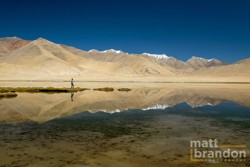Alou Brandon stands on the lakes edge in Ladakh, India, high in the Himalaya.