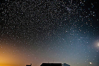 Stary night sky above the Mount Tahoma Trails High Hut with Mount Rainier in the background as well as the glow on the horizon from Seattle Lights.