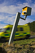 Ambulance passes vandalised Gatso speed camera on A40, Oxfordshire, England, United Kingdom