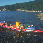 Duncan Murrell's fully loaded Nautiraid folding kayak, Hoonah, Admiralty Island, Southeast Alaska, USA.<br /> <br /> Although I had progressed to using a larger kayak it was still a challenge to get everything in, including myself. The wheels are for a kayak cart that didn't survive very long. I usually used two inverted polystyrene crab-pot floats as rollers to haul my kayak up the rocky beaches. There were very few, clear flat beaches available anywhere to make it any easier to move my kayak up and down. Packing and launching, and then beaching and unloading was always a major work-out, done the hard way of course.
