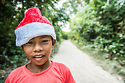 A young Khmer boy with Santa hat walking on a dirt trail in rural Cambodia.