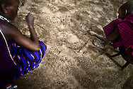 Tanzania, traditional Maasai life. Laurusai illustrating a homework problem for Tobiko in the sand.