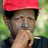 Michael Neal, a homeless resident in Tupelo sits in the shade as he smokes his cigarette.