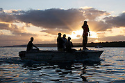 Five men in a boat silhouetted against the setting sun in Port Vila, Vanuatu.