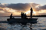 Five men in a boat silhouetted against the setting sun in Port Vila, Vanuatu.