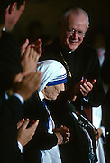 Cardinal James Hickey, Archbishop of Washington applauds Mother Teresa, founder of the Missions of Charity order as she receives the Congressional Medal of Honor during a ceremony in the U.S. Capitol May 6, 1997 in Washington, DC.