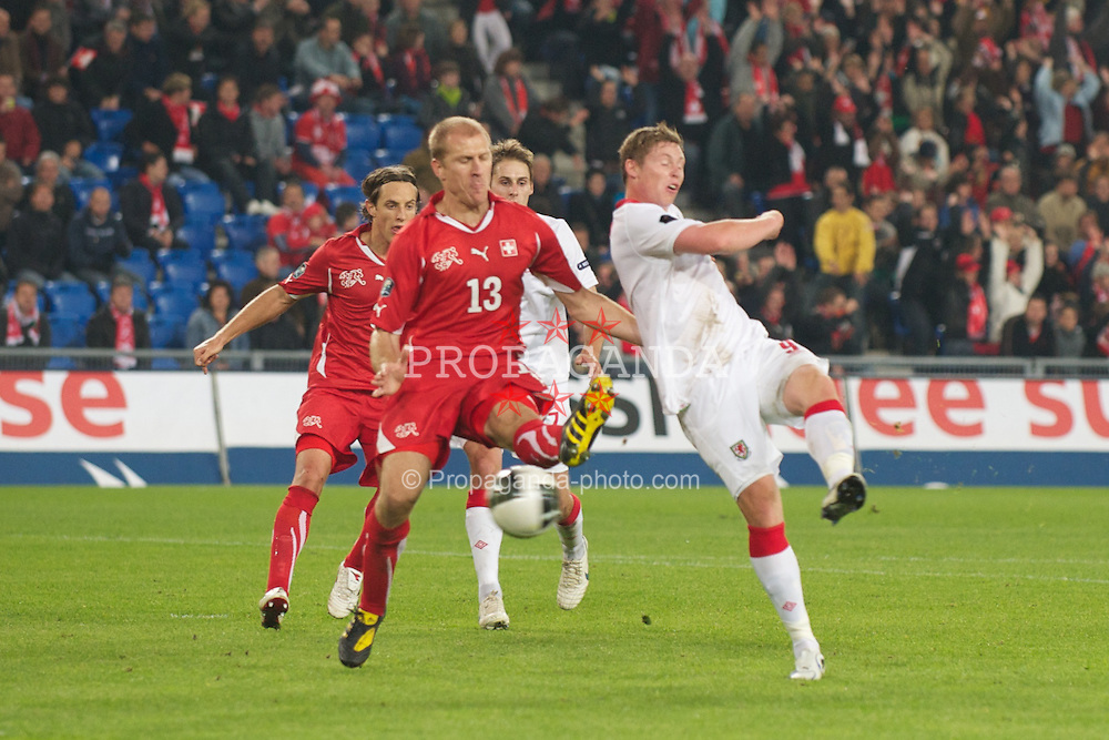 BASEL, SWITZERLAND - Tuesday, October 12, 2010: Wales' Simon Church puts his shot over the bar under pressure from Switzerland's Stephane Grichting during the UEFA Euro 2012 qualifying Group G match at St. Jakob-Park. (Pic by David Rawcliffe/Propaganda)