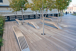 Wooden seating at  new High Line elevated landscaped public walkway built on old railway viaduct in Chelsea district of Manhattan in New York City USA