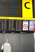 "An upright picture of a departures information board at Heathrow Airport's Terminal 5. A lady passenger stands motionless to read the details of flight departure times to echo that of a Vodafone advertisement containing a figure of a man standing erect on a beach, a generic scene of a person on holiday taking advantage of low mobile phone charges in mainland Europe.  Both the man and the woman are on opposite sides of the picture and we see a large letter C that denotes the check-in zone of this 400 metre-long terminal that has the capacity to serve around 30 million passengers a year. From writer Alain de Botton's book project ""A Week at the Airport: A Heathrow Diary"" (2009). .."