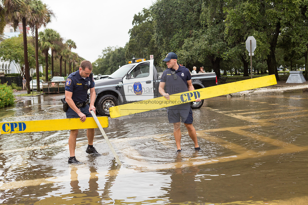 Police erect a barrier to stop vehicles from driving flooded streets in the historic district as Hurricane Joaquin brings heavy rain, flooding and strong winds as it passes offshore October 4, 2015 in Charleston, South Carolina.