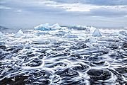 The ocean surf and fragments of icebergs on the black sand beach at the end of the glacial lagoon in Jokulsarlon, Iceland.