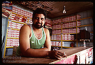 Cigarette vendor smokes in his store, surrounded by cigarette cartons; Eirunepe, Amazonas. Brazil