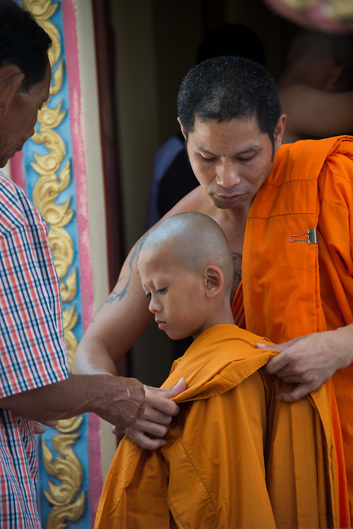 A young man learns to dress in the robes of a monk in  Rural Nakhon Nayok, Thailand.