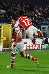 Arsenal's Lukas Podolski scores his winning goal in the last minute of the game with Arsenal's Alexis Sanchez - Photo mandatory by-line: Dougie Allward/JMP - Mobile: 07966 386802 - 22/10/2014 - SPORT - Football - Anderlecht - Constant Vanden Stockstadion - R.S.C. Anderlecht v Arsenal - UEFA Champions League - Group D