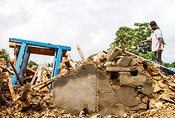 © London News Pictures. 30/04/201530th April 2015: NEPAL: A M7.9 earthquake struck on Saturday 25th April, causing widespread devastation across the country creating an international humanitarian emergency. Here in the remote village of Sindhupalchowk a man begins to clear his destroyed home. Photo Credit: Sam Spikett/LNP