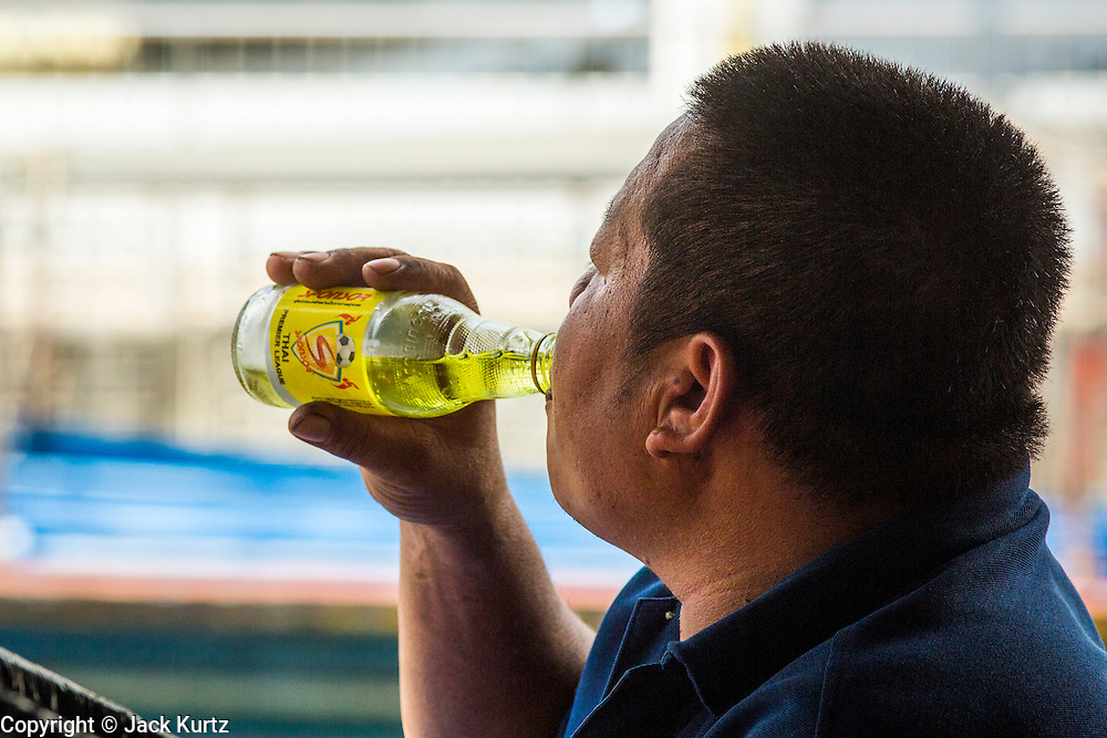 14 NOVEMBER 2012 - BANGKOK, THAILAND: A passenger boat driver drinks a Thai energy drink before starting his run into Bangkok from the Wat Sriboonreung Pier, the southern terminal of the Khlong Saen Saeb boat service. Bangkok used to be criss crossed by canals (called Khlongs in Thai) but most have been filled in and paved over. Khlong Saen Saeb is one of the few remaining khlongs in Bangkok with regular passenger boat service. Boats and ships play an important in daily life in Bangkok. Thousands of people commute to work daily on the Chao Phraya Express Boats and fast boats that ply Khlong Saen Saeb. Boats are used to haul commodities through the city to deep water ports for export.      PHOTO BY JACK KURTZ