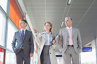 Business people discussing while walking on train platform