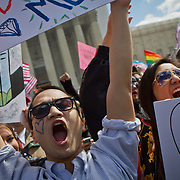 Tyler Pham, a student from American University, left, joins Michelle Le, in demonstrating outside the Supreme Court during the hearings for the Defense of Marriage Act (DOMA), on Wednesday, March 27, 2013.