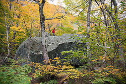 "A hiker explores the Smugglers' Cave area at the top of Smugglers' Notch, the highlight of Vermpnt State Highway 108.  The area comprises a huge boulder field with trees adding grace notes.<br /> From Wikipedia: ...""a narrow notch (mountain pass) running adjacent to Sterling Mountain, which smugglers used many years ago. Smugglers' Notch is nicknamed Smuggs. It consists of three mountains: Morse Mountain, Madonna and Sterling Mountains."