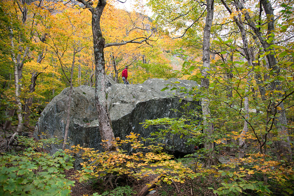 A hiker explores the Smugglers' Cave area at the top of Smugglers' Notch, the highlight of Vermpnt State Highway 108.  The area comprises a huge boulder field with trees adding grace notes.<br /> From Wikipedia: ...&quot;a narrow notch (mountain pass) running adjacent to Sterling Mountain, which smugglers used many years ago. Smugglers' Notch is nicknamed Smuggs. It consists of three mountains: Morse Mountain, Madonna and Sterling Mountains.