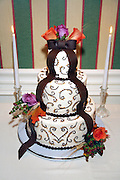 Fall wedding cake with scrollwork, brown fondant ribbon and rose decorations sitting between two taper candles, Colgate Inn, Hamilton, NY