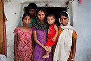 Sadma Khan (in purple), 19, stands with her immediate family for a family portrait at the door of her shared house in her mother's (in orange) extended family's compound in a slum area of Tonk, Rajasthan, India, on 19th June 2012. She was married at 17 years old to Waseem Khan, also underaged at the time of their wedding. The couple have an 18 month old baby (in red) and Sadma is now 3 months pregnant with her 2nd child and plans to use contraceptives after this pregnancy. She lives with her mother since Waseem works in another district and she can't take care of her children on her own. Photo by Suzanne Lee for Save The Children UK