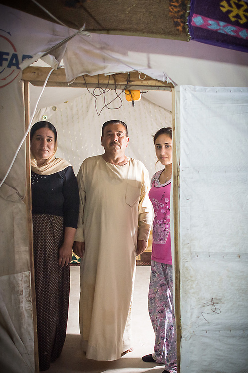 Seido (left) and Basi (right) stand with one of their daughters in front of their tent in Sharia Camp near Dohuk. As soon as Shingal region is safe and when there are schools, medical care and international protection for the Yazidis, they want to return with their eleven children to their home village Snune, that lies north of the Mount Shingal. Shariya, Iraq, July 17, 2016