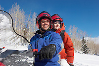 Couple Sitting on Snowmobile in snow
