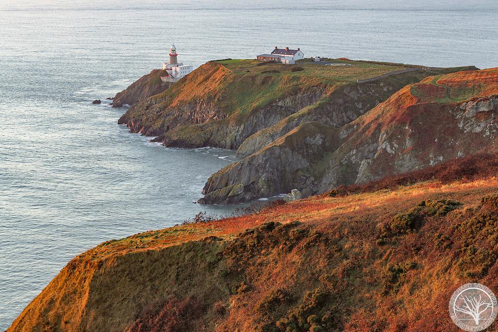 The lighthouse at Howth Headland illuminated by beautiful sunrise light. Howth, Ireland