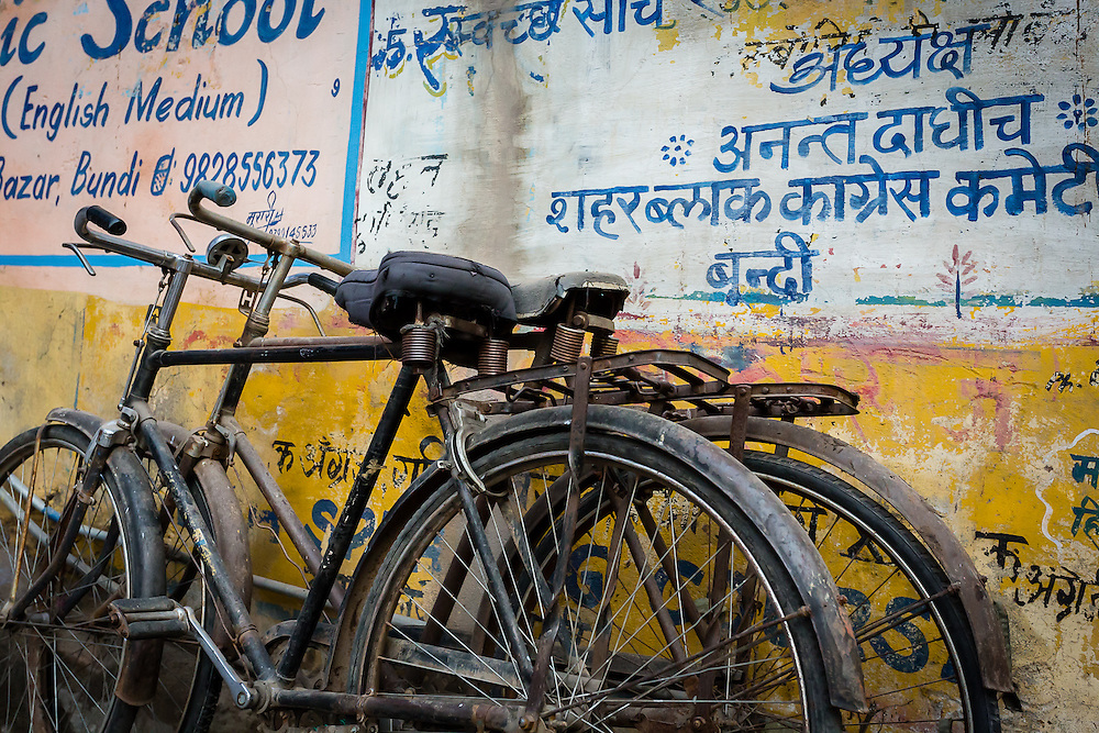 A pair of bycicles stands against a yello wall covered in advertisements, some in english, some in hindi.