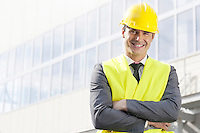 Portrait of smiling young male architect standing arms crossed outside office building