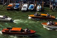 Impatto del turismo di massa. Traffico nel Canal Grande, presso il Ponte di Rialto. L'incremento del numero di turisti ha comportato una maggiore presenza di taxi d'acqua nei canali, con conseguenze sull'erosione delle fondamenta della città.