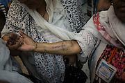 Una pellegrina etiope mostra il suo tatuaggio ai compagni di viaggio