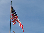 A weathered ripped flag on a flagpole against a blue sky.