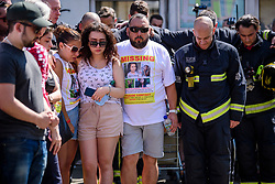 © Licensed to London News Pictures. 19/06/2017. London, UK. Family of fire victim Jessica Urbano are joined by firefighters who attended the scene, at a minutes silence held near the scene of the Grenfell tower block fire. The blaze engulfed the 27-storey building killing dozens - with 34 people still in hospital, many of whom are in critical condition. Photo credit: Ben Cawthra/LNP