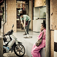 Woman sitting streetside in Little India, Kuala Lumpur