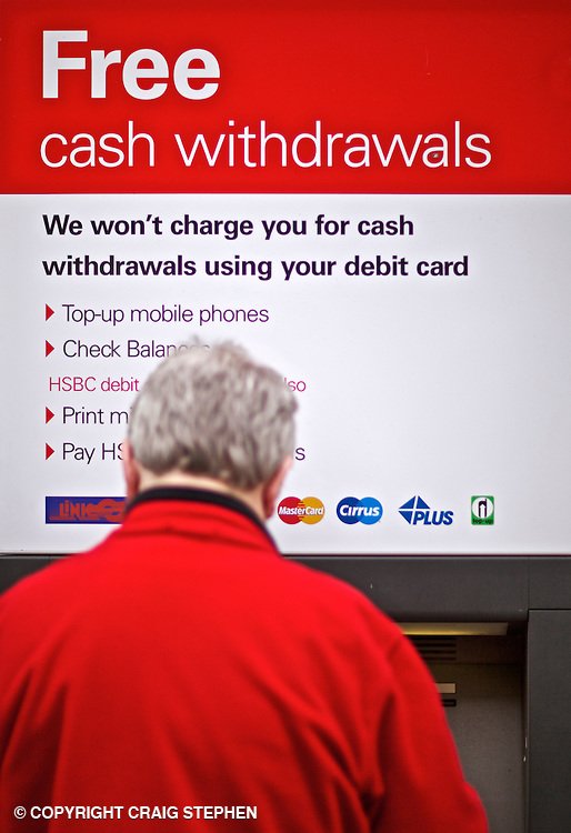 Man using an ATM / cash machine offering free withdrawals