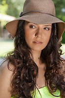 Beautiful young woman wearing sunhat looking away in park