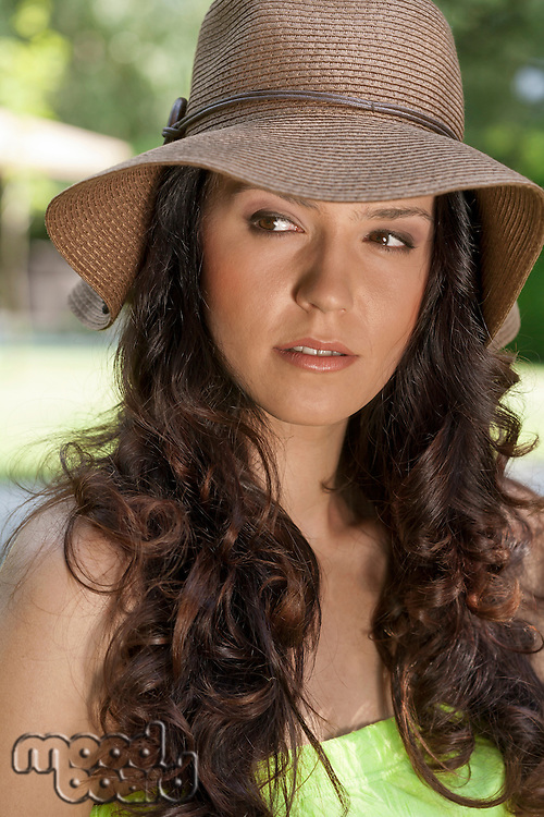 Beautiful young woman wearing sunhat looking away in park