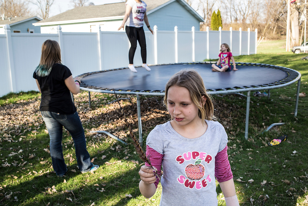 Girls play with a found feather and trampoline in their back yard on Sunday, April 28, 2013 in Webster City, IA.