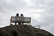 couple sitting on bench on top of a hill