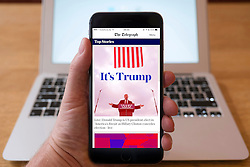 Detail of iPhone smart phone showing online mobile  newspaper front-page headline from The Telegraph following Donald Trump's victory in 2016 US Presidential Election