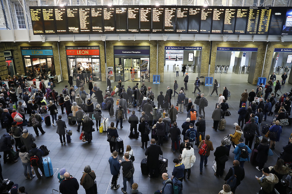 © Licensed to London News Pictures. 23/12/2016. London, UK. Passengers wait for trains at King's Cross station. The Christmas getaway begins  today with<br /> stations, airports and roads expected to be very busy as people start their Christmas holidays. Photo credit: Peter Macdiarmid/LNP