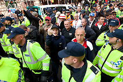 © Licensed to London News Pictures. 02/06/2012. Brighton, UK. Supporters of he EDL and other nationalist groupsare lead through streets in Brighton as those who oppose them look on. Photo credit : Joel Goodman/LNP