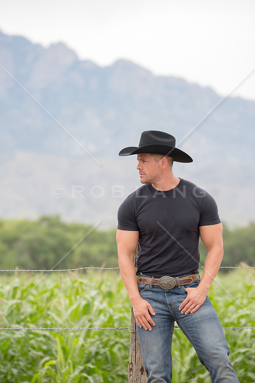 rugged cowboy in a black tee shirt on a ranch with mountain views