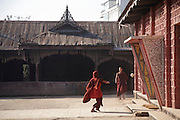 Young monks kicking a ball in a yard outside a monastery in Nyuangshwe, Myanmar (Burma).