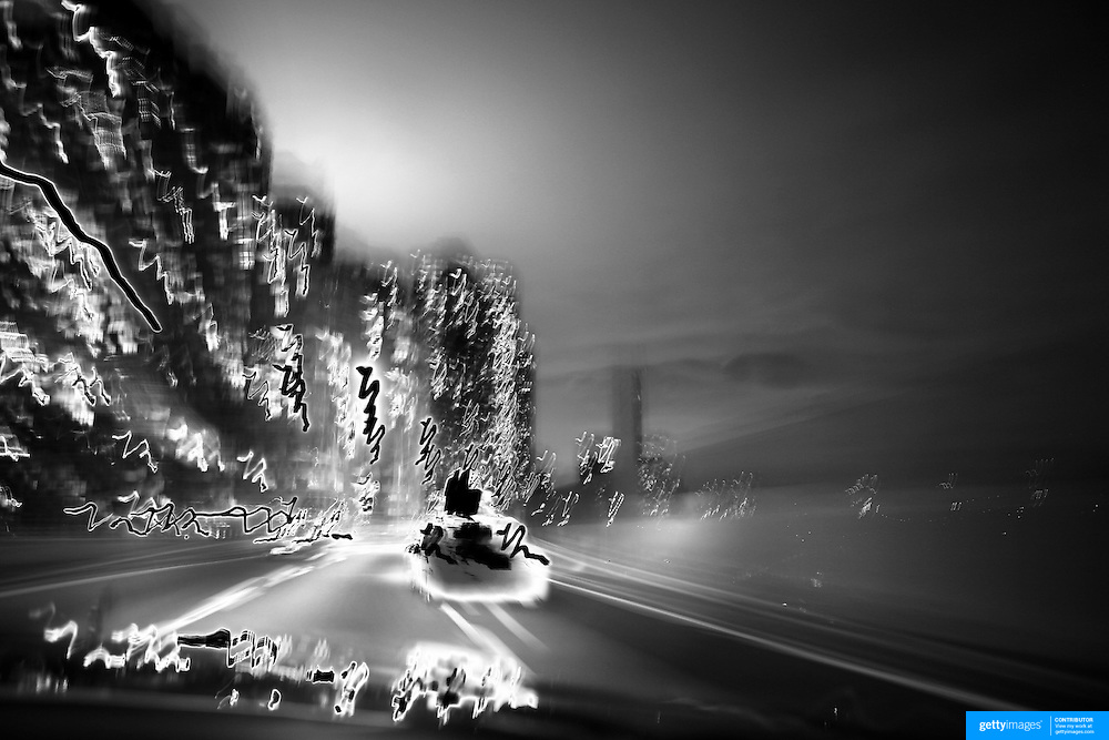 A Black and White image of a New York Taxi cab showing motion and movement as it navigates through the city lights and metropolis of the big city at night time. New York, USA. 26th October 2012. Photo Tim Clayton